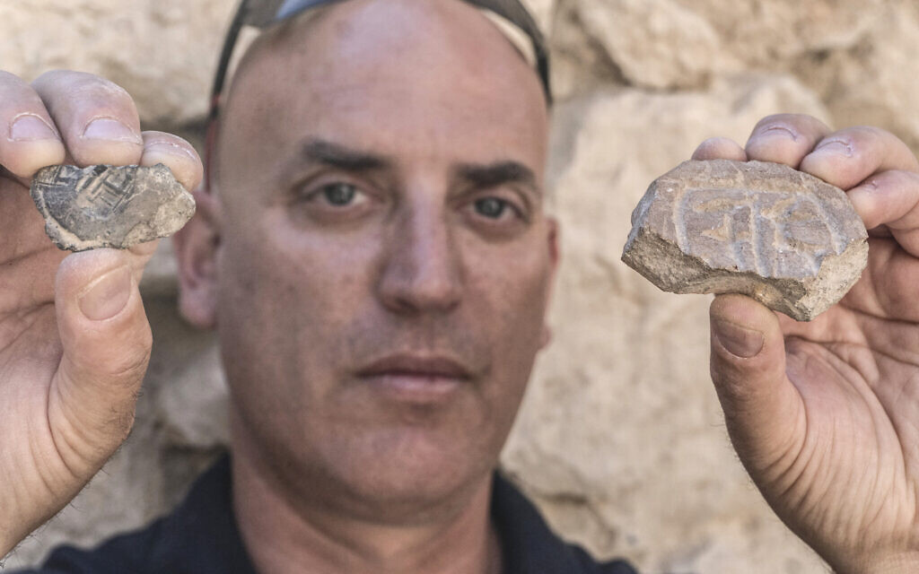 Israel Antiquities Authority's Dr. Yiftah Shalev with the Persian-era seal and seal impression discovered in the City of David's Givati Parking Lot excavations.  (Shai Halevy, Israel Antiquities Authority)
