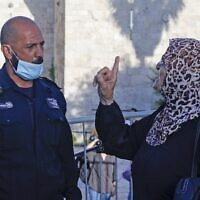 A Palestinian woman argues with a member of Israeli security forces, as she takes part in a protest at the Damascus Gate of the Old City of Jerusalem, on May 31, 2020, to condemn the shooting a day earlier of Iyad Hallak, a disabled Palestinian man who was shot dead by Israeli police. (AHMAD GHARABLI / AFP)
