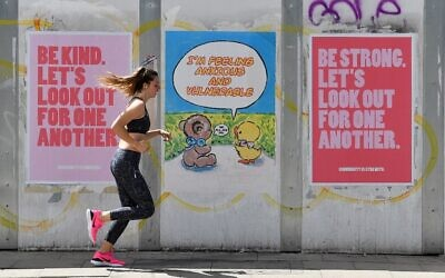 A woman runs to exercise past posters promoting community spirit, erected during the novel coronavirus COVID-19 pandemic, in Manchester, northern England on June 2, 2020. (Paul ELLIS / AFP)