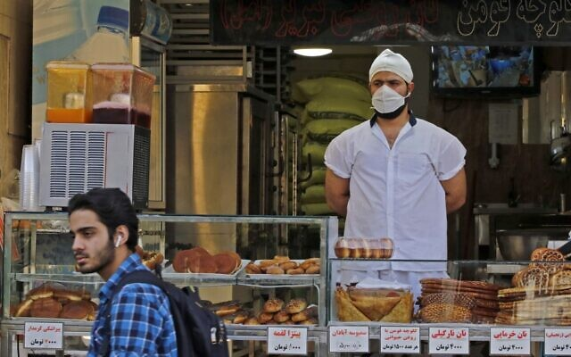 An Iranian man walks in front of a pastry shop in the capital Tehran on June 3, 2020, amid the coronavirus pandemic. (AFP)