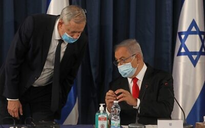 Prime Minister Benjamin Netanyahu (R) speaks with Alternate PM and Defense Minister Benny Gantz, both wearing protective mask due to the ongoing COVID-19 pandemic, during the weekly cabinet meeting in Jerusalem on June 7, 2020. (Menahem KAHANA / AFP)