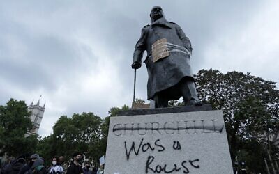 The statue of former British prime minister Winston Churchill is seen defaced, with the words (Churchill) 'was a racist' written on its base in Parliament Square, London, on June 7, 2020 (ISABEL INFANTES / AFP)