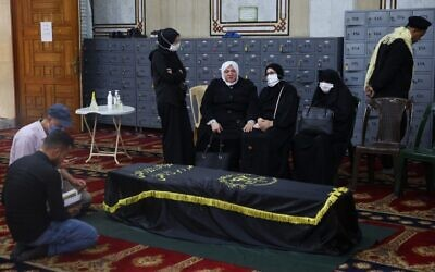Mourners pray over the coffin of Ramadan Shalah, former leader of the Palestinian Islamic Jihad terror group, during his funeral in the Syrian capital Damascus on June 7, 2020. (AFP)