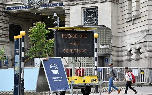 A sign tells passengers to 'wear a face covering' at Waterloo train station in central London , on June 8, 2020, as the UK government's planned 14-day quarantine for international arrivals to limit the spread of the novel coronavirus COVID-19 begins. (Photo by JUSTIN TALLIS / AFP)