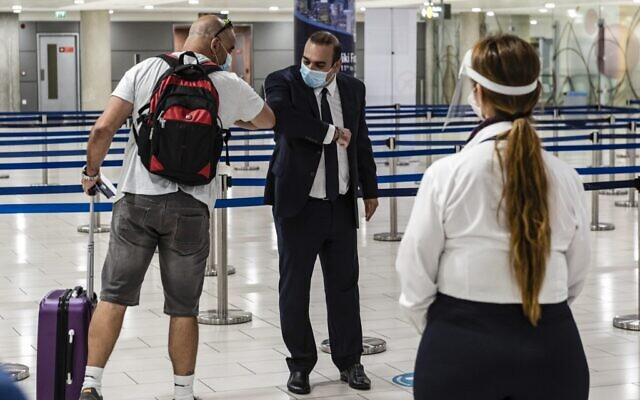 Yiannis Karoussos (C), Cyprus' minister of Transport, Communications, and Works, greets with an 'elbow shake' the first passenger arriving from Israel at Cyprus's Larnaca International Airport on June 9, 2020 (Iakovos HATZISTAVROU / AFP)