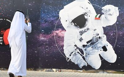 Illustrative -- In this file photo taken on September 25, 2019 a man takes a picture of an illustration depicting an astronaut with the Emirati national flag outside Mohammed Bin Rashid Space Centre (MBRSC) in Dubai (KARIM  SAHIB / AFP)