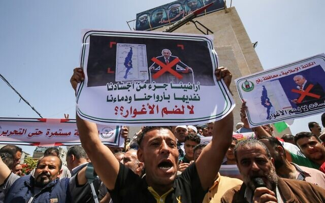 Palestinians lift placards during a protest against Israel's plans to annex parts of the West Bank, at Rafah in the southern Gaza Strip, on June 11, 2020. (Said Khatib/AFP)