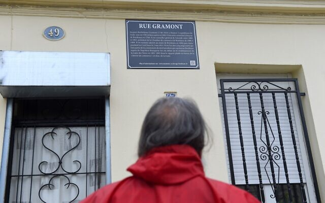 A man looks at a street plaque on the rue Gramont in Bordeaux, on June 11, 2020, set up as part of new explanatory versions of street plaques bearing the names of city historical figures who took part in slave trade. (NICOLAS TUCAT / AFP)