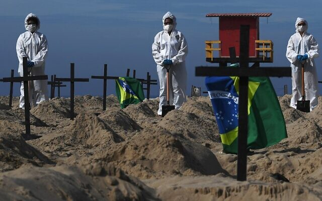 Activists from the Brazilian NGO Rio de Paz (Peace Rio), stand next to 100 mock graves on Copacabana beach symbolizing deaths from the COVID-19 coronavirus in Rio de Janeiro, Brazil, on June 11, 2020, to protest against Brazil's 'bad governance' of the pandemic (CARL DE SOUZA / AFP)