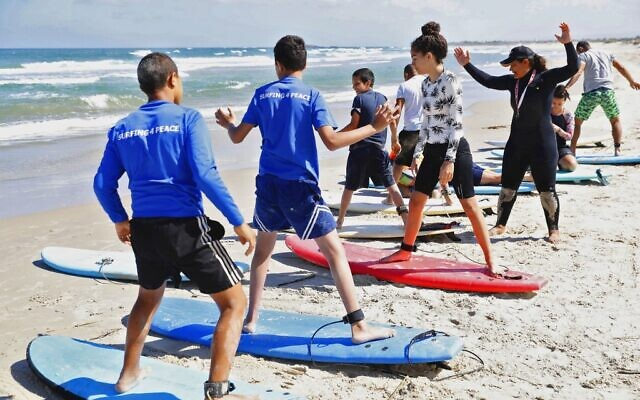 Hamama Jarban (R), 41, a lifeguard angler and surf teacher, gives surf lessons on June 12, 2020 on the beach in the coastal village of Jisr az-Zarqa (JACK GUEZ / AFP)