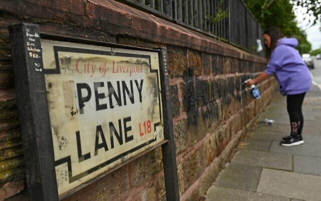 A local resident cleans graffiti from a wall on Penny Lane in Liverpool, north west England on June 12, 2020, after a wall and street signs were defaced (Oli SCARFF / AFP)