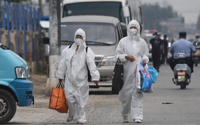Two women wear protective suits as they walk on a street near the closed Xinfadi market in Beijing on June 13, 2020. (GREG BAKER / AFP)
