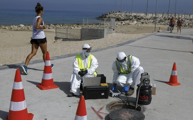 Technicians from Israeli firm Kando extract sewage samples from a manhole near the beach, in the southern coastal city of Ashkelon, on June 11, 2020. (MENAHEM KAHANA/AFP)