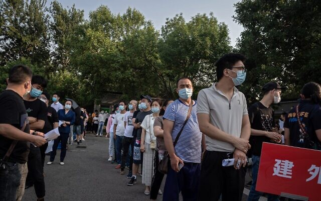 A group of people wearing face masks wait in a queue to undergo COVID-19 coronavirus tests in Beijing on June 19, 2020 (NICOLAS ASFOURI / AFP)