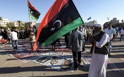 """A man waves a Libyan natioanl flag as people walk on protest signs showing """"X"""" marks on the faces of (R to L) French President Emmanuel Macron, Egyptian President Abdelfattah el-Sisi, and Abu Dhabi's Crown Prince Sheikh Mohammed bin Zayed Al Nahyan, during a demonstration in the Martyrs' Square in the centre of the Libyan capital Tripoli, currently held by the UN-recognised Government of National Accord (GNA), on June 21, 2020.  (Photo by Mahmud TURKIA / AFP)"""
