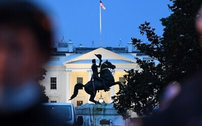 A row of police officers stand guard with the equestrian statue of former US President General Andrew Jackson behind, after protesters tried to topple it, at Lafayette square, in front of the White House, in Washington, DC on June 22, 2020 (Eric BARADAT / AFP)