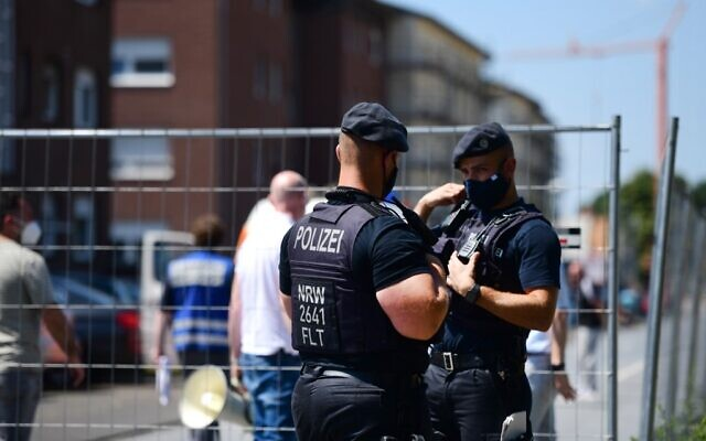 Police officers stand guard near the residential homes of the employees of Toennies abatoir, in Verl, western Germany on June 23, 2020, amid the novel coronavirus pandemic. (FASSBENDER/AFP)
