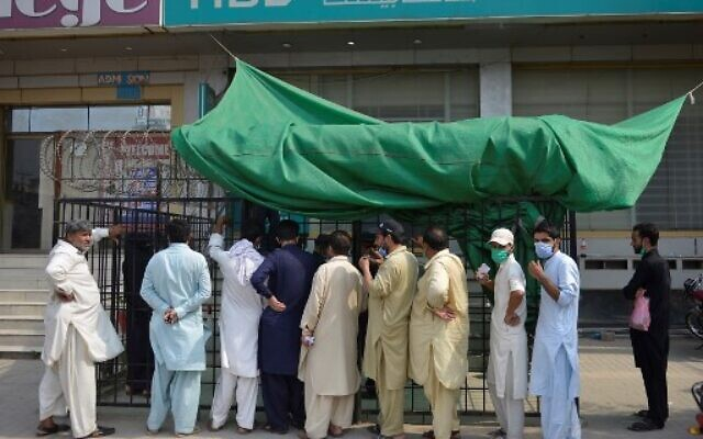 People wait for their turn outside a bank in Islamabad on June 23, 2020, after the COVID-19 coronavirus cases continue to rise. (Farooq NAEEM / AFP)