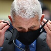 Director of the National Institute for Allergy and Infectious Diseases Dr. Anthony Fauci takes off his face before he testifies before the US Senate Health, Education, Labor, and Pensions Committee hearing to examine COVID-19, on June 23, 2020. (KEVIN DIETSCH / POOL / AFP)