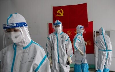 """Illustrative: Medics from Beijing Fengsheng Special Hospital of Traditional Medical Traumatology and Orthopaedics prepare for their shift at the Jinrong Street testing site, inside a room where a Communist Party flag and a piece of red tissue with words that reads """"Beijing Fengsheng Special Hospital of Traditional Medical Traumatology and Orthopaedics"""" (back on wall) in Beijing on June 24, 2020. (NICOLAS ASFOURI / AFP)"""