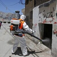 A worker of the Palestinian Bethlehem municipality in cooperation with the popular committee of Aida Refugee Camp sterilizes a street against coronavirus on June 25, 2020 in the Aida Refugee Camp near the West Bank city of Bethlehem (Musa Al SHAER / AFP)
