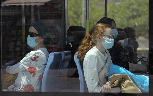 Israelis wearing protective masks ride the light rail train in Jerusalem on June 28, 2020. (Menahem Kahana/AFP)