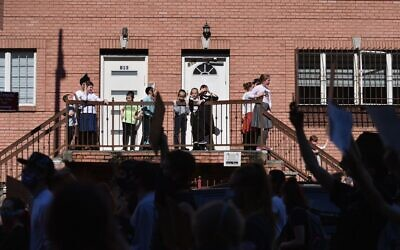 """Illustrative: Members of the Orthodox Jewish community watch as protesters walk through the Brooklyn borough on June 3, 2020, during a """"Breonna Taylor and Black Lives Matter"""" protest in New York City, after the recent death in Minneapolis police custody of George Floyd. (Photo by Angela Weiss / AFP)"""