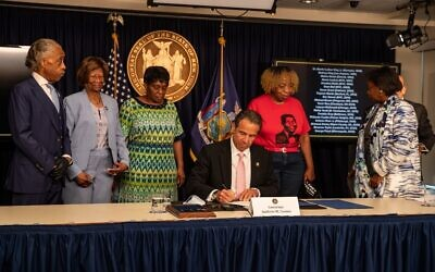 New York Governor Andrew Cuomo signs the 'Say Their Name' reform during the daily media briefing as he is joined by (L-R) Rev. Al Sharpton, Dr. Hazel N. Dukes, Valerie Bell; the mother of Sean Bell, Gwen Carr; the mother of Eric Garner, and NY State Sen. Andrea Stewart- Cousins at the Office of the Governor of the State of New York on June 12, 2020 in New York City. (Jeenah Moon/Getty Images/AFP)