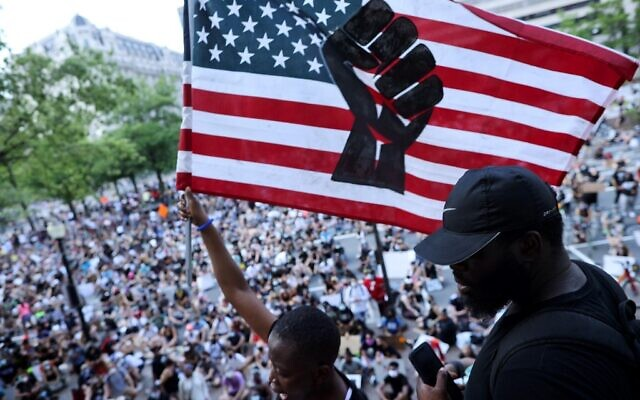 Pilomena Wankenge of the DC Freedom Fighters waves an American flag to a crowd gathered at the John A. Wilson Building during a protest against police brutality and racism on June 6, 2020 in Washington, DC. (Chip Somodevilla/Getty Images/AFP)