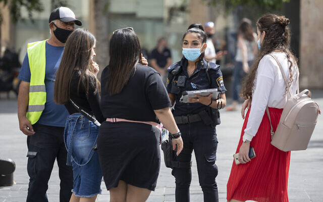 A police officer gives fines to young women for not properly wearing their face masks in the city center of Jerusalem on June 11, 2020. (Olivier Fitoussi/Flash90)