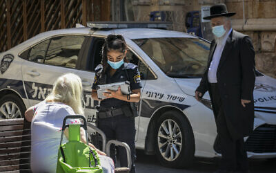 A police officer writes up a fine for a woman who was not wearing a mask in Jerusalem on June 24, 2020. (Olivier Fitoussi/Flash90)