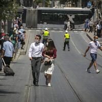 people wearing face masks walk in Jerusalem on June 24, 2020. (Olivier Fitoussi/Flash90)