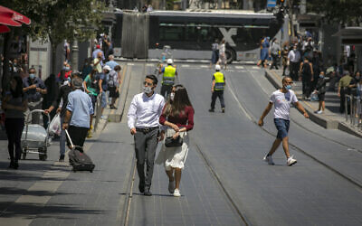 people wearing face masks walk in Jerusalem on June 24, 2020. (Olivier Fitoussi/Flash90)