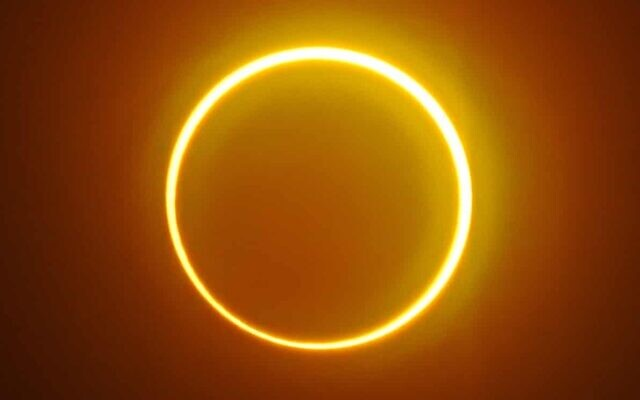 """The moon moves in front of the sun in a """"ring of fire"""" solar eclipse as seen from Balut Island in the southern Philippines on Dec 26, 2019. (AFP Photo)"""