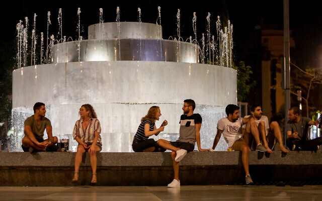 People sit at Dizengoff Square in Tel Aviv with drinks from home and the surrounding bars, May 18, 2020. Lockdown restrictions have been partly removed. (Guy Prives/Getty Images/ via JTA)