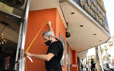 Marc Canter measures in case he needs to board up the doors and windows at Canter's Deli on Fairfax on Sunday, May 31, 2020. (Christina House / Los Angeles Times via Getty Images via JTA)