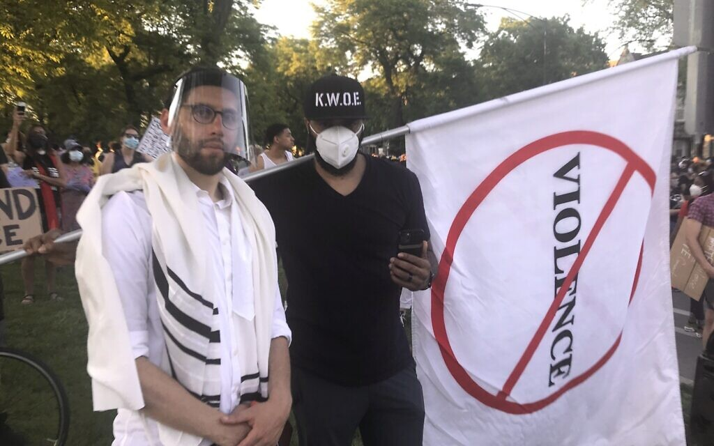 Rabbi Ari Hart, wearing a prayer shawl and face shield, stands with another protester at the interfaith demonstration in memory of George Floyd and protesting systemic racism in Chicago on June 2, 2020. (Courtesy of Hart/ via JTA)