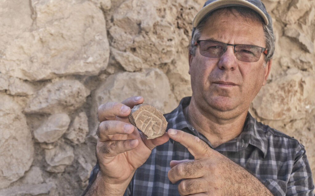 Tel Aviv University Prof. Yuval Gadot with the Persian-era seal and seal impression discovered in the City of David's Givati Parking Lot excavations.  (Shai Halevy, Israel Antiquities Authority)