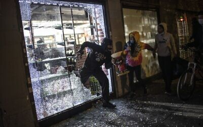 People run out of a shop after breaking in as police arrive at the scene in New York, June 1, 2020. (Wong Maye-E/AP)