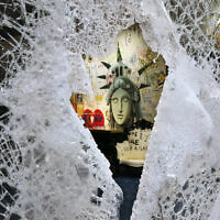 A Statue of Liberty painting is seen through a smashed Dolce and Gabbana store window, June 1, 2020, in the SoHo neighbourhood of New York. (Mark Lennihan/AP)