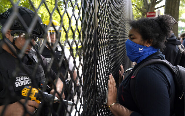 A demonstrator watches as a US Secret Service police office works on a fence blocking Lafayette Park as protests in the death of George Floyd continue, Tuesday, June 2, 2020, near the White House in Washington. Floyd died after being restrained by Minneapolis police officers. (AP Photo/Evan Vucci)