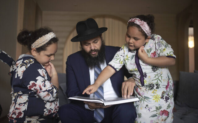 Rabbi Levi Banon and his daughters read a book inside their home in Casablanca, Morocco, May 28, 2020. (AP Photo/Mosa'ab Elshamy)
