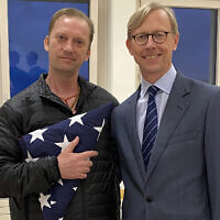 In this image provided by the U.S. State Department, Michael White holds an American flag as he poses for a photo on June 4, 2020, with US special envoy for Iran Brian Hook at the Zurich, Switzerland, airport after White's release from Iran. (US State Department via AP)
