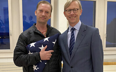 In this image provided by the US State Department, Michael White holds an American flag as he poses for a photo on June 4, 2020, with US special envoy for Iran Brian Hook at the Zurich, Switzerland, airport after White's release from Iran. (US State Department via AP)