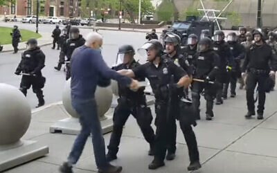 In this image from video provided by WBFO, a Buffalo police officer appears to shove a man who walked up to police Thursday, June 4, 2020, in Buffalo, N.Y. Video from WBFO shows the man appearing to hit his head on the pavement, with blood leaking out as officers walk past to clear Niagara Square.  (Mike Desmond/WBFO via AP)