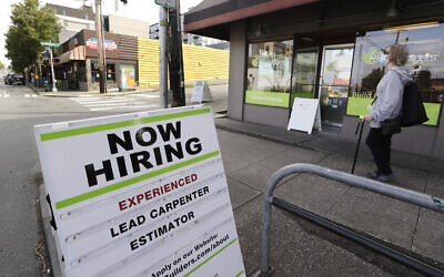 In this photo taken Thursday, June 4, 2020, a pedestrian wearing a mask walks past reader board advertising a job opening for a remodeling company, in Seattle. (AP Photo/Elaine Thompson)