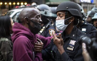 In this June 2, 2020, file photo, a protester and a police officer greet in the middle of a standoff during a solidarity rally calling for justice over the death of George Floyd in New York (AP Photo/Wong Maye-E, File)
