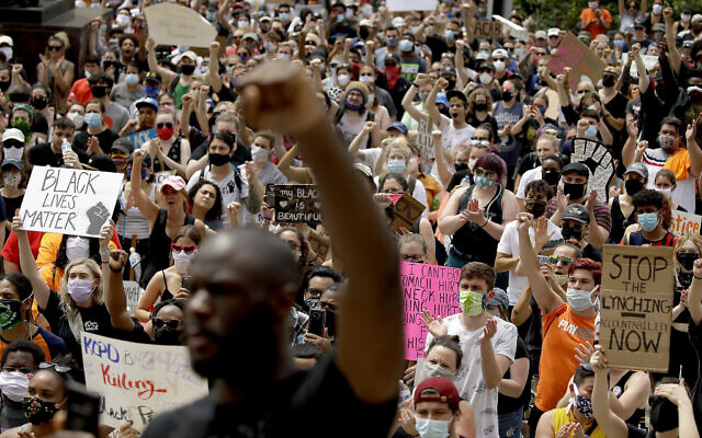 People hold signs as they listen to a speaker in front of city hall in downtown Kansas City, Missouri., Friday, June 5, 2020 (AP Photo/Charlie Riedel)