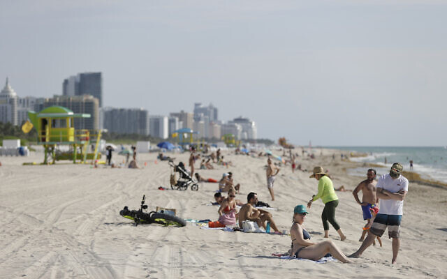 Beach goers in Miami-Dade County enjoy a day on the sand and in the water, on Wednesday, June 10, 2020 (AP Photo/Wilfredo Lee)