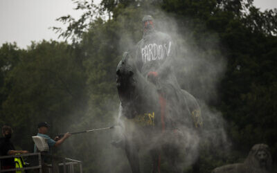 Workers clean graffiti from a statue of Belgium's King Leopold II in Brussels on June 11, 2020, that was targeted by protesters during a Black Lives Matter demonstration (AP Photo/Francisco Seco)